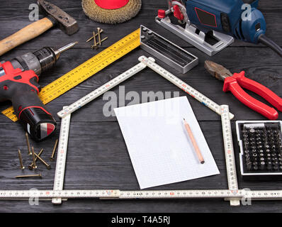white sheet in a cell for writing with a pencil on the background of a hand-held construction tool on black old boards - Stock Photo