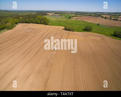 modern tractor working on the agricultural field - tractor plowing and sowing in the agricultural field - aerial view - high view - Stock Photo