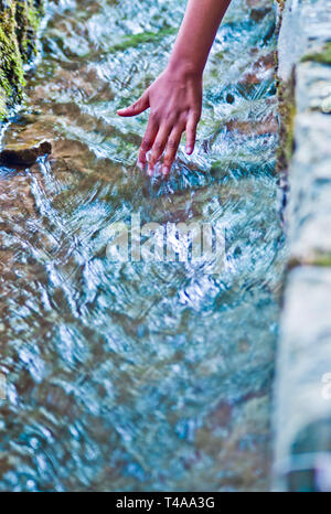 water, source of life, and hand of a young boy - Stock Photo