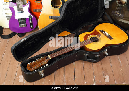 Musical instrument - Vintage twelve-string acoustic guitar hard case on a guitar and wooden background. Stock Photo