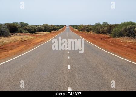 Long straight road leading through the dry Australian Bush land - Stock Photo