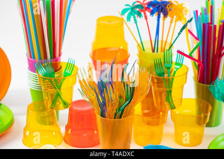 Plastic bright forks placed into transparent cups with dangerous straws - Stock Photo