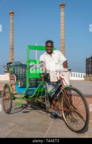Vertical view of a cycle rickshaw owner and his vehicle in Pondicherry, India. - Stock Photo