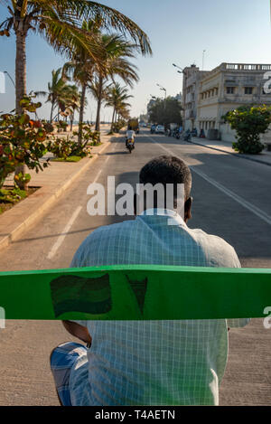 Vertical streetview from the back of a cycle rickshaw in Pondicherry, India. - Stock Photo