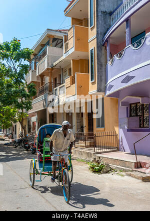 Vertical typical streetview in Pondicherry with a cycle rickshaw going by. - Stock Photo