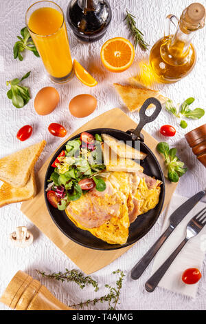 Ham and egg omelette, delicious and simple with fresh toast bread and fresh salad served with fresh orange juice - Stock Photo