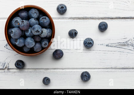 blueberries spilling out of a bowl on distressed white wooden background - Stock Photo
