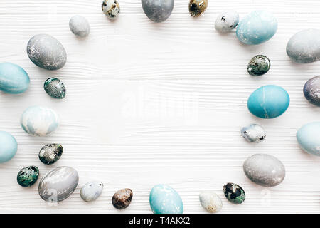 Happy Easter, greeting card mockup. Stylish Easter eggs frame, flat lay on white wooden background with space for text. Modern easter eggs painted wit - Stock Photo