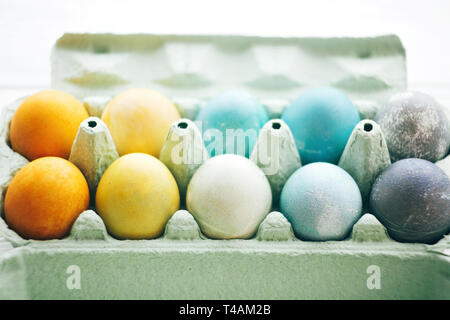 Stylish Easter eggs in carton tray on white wooden background, space for text. Modern colorful easter eggs painted with pastel natural dye in rainbow  - Stock Photo