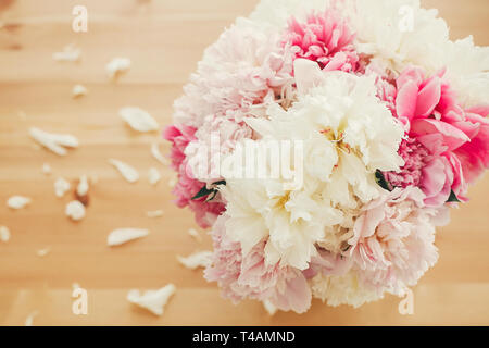 Stylish pink and white peonies in vase on wooden table with petals, flat lay with space for text. Happy mother's day. International womens day. Greeti - Stock Photo