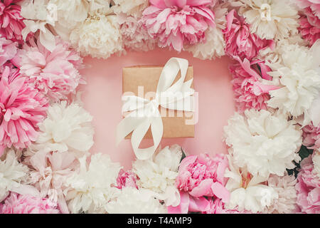 Gift box in stylish pink and white peonies frame on pink paper flat lay. Happy mother's day. International womens day. Greeting card mockup. - Stock Photo