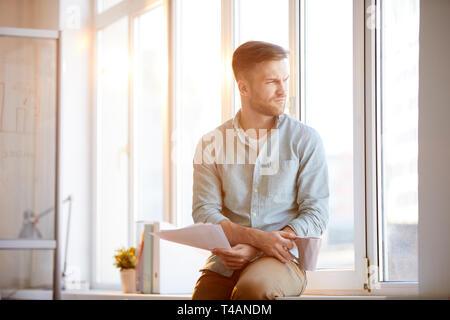 Pensive Businessman Sitting by Window