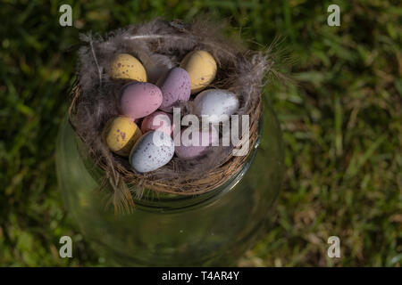 Mini chocolate eggs in a nest with bird feathers sitting on top of a glass jar on the grass. Religion/food and drink. - Stock Photo