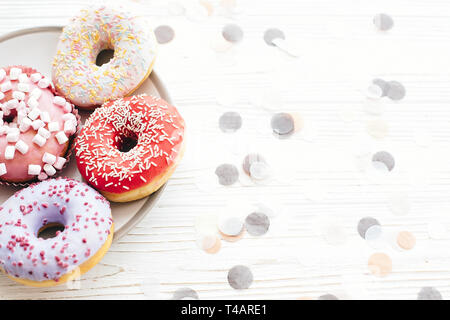 Delicious colorful donuts with sprinkles and marshmallows on stylish plate on white table with confetti. Party concept. No diet. Candy bar at wedding  - Stock Photo