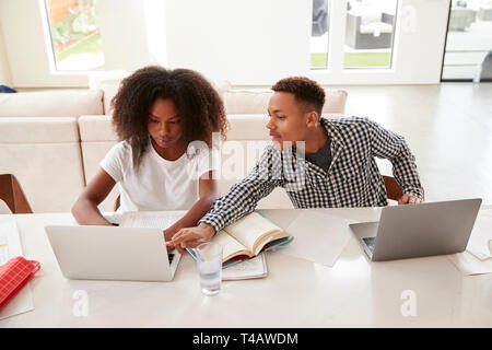 Teenage boy helping his younger sister with her homework, both using laptops, elevated view - Stock Photo