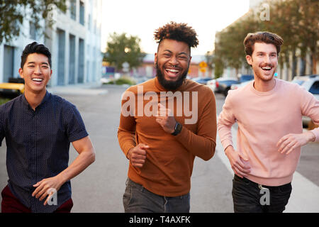 Three hip young adult male friends running for fun in a city road, front view, close up