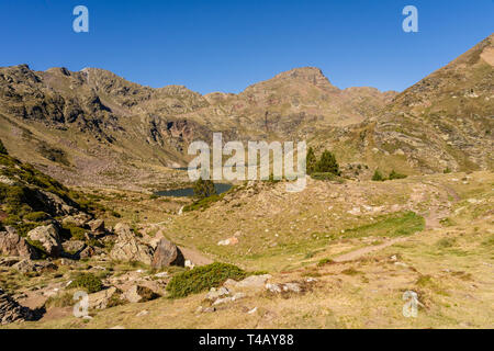 Wooden bridge in the hiking trail Estanys de Tristaina, Pyrenees, Andorra - Stock Photo