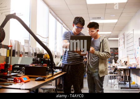 Two Male College Students Using Laptop Computer In Science Robotics Or Engineering Class - Stock Photo