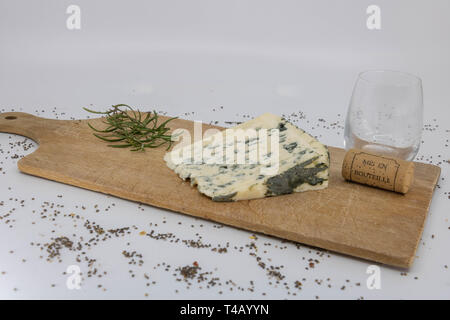 French wine and cheese at the end of a meal on a wooden cutting board - Stock Photo
