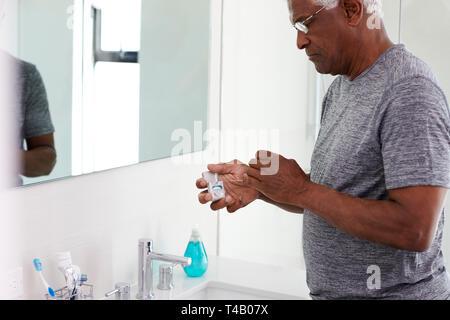 Senior Man Flossing Teeth Standing Next To Bathroom Mirror Wearing Pajamas - Stock Photo