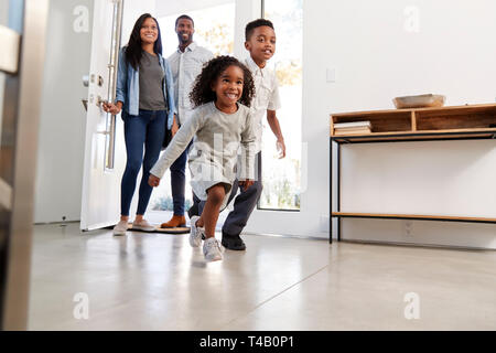 Parents And Children Returning Home Opening Front Door And Running Inside - Stock Photo