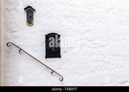 Rock wall painted in white with railing and two letter boxes for mediterranean style. - Stock Photo