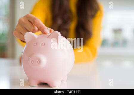 Close up of woman putting a coin inside piggy bank as investment - Stock Photo