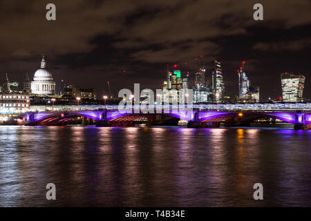 London night cityscape with Blackfriars bridge and the brightly lit skyscrapers of the city, and St Pauls cathedral reflected on to the River Thames a - Stock Photo