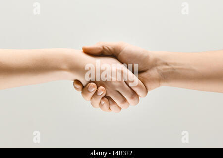 Sign of joint plans for the future. Teamwork and communications. Two male hands shaking isolated on grey studio background. Concept of help, partnership, friendship, relation, business, togetherness. - Stock Photo
