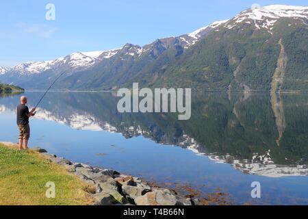 HARDANGER FIORD, NORWAY - JULY 17, 2015: Man enjoys angling at Sorfjord part of Hardanger Fiord, Norway. Foreign tourists spent some 5 million overnig - Stock Photo