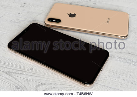 Bucharest, Romania - April 2019: Apple iPhone XS gold smartphone, comparison of front and rear side by side on a white wood background. Blank screen - Stock Photo