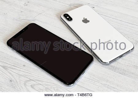 Bucharest, Romania - April 2019: Apple iPhone XS silver smartphone, comparison of front and rear side by side on a white wood background. Blank screen - Stock Photo