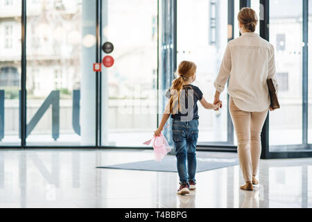 A rear view of businesswoman with small daughter walking in office building. - Stock Photo