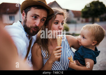 Parents and small toddler girl with ice cream outdoors in summer, taking selfie. - Stock Photo