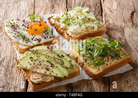 Open sandwiches with hummus, avocado, feta cheese, microgreen and egg closeup on the table. horizontal - Stock Photo