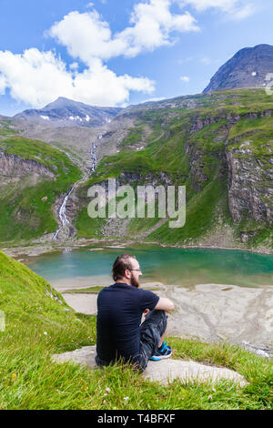 A young man enyojing the view to the the lake called Nassfeld Speicher in Hohe Tauern National Park in Austria - Stock Photo