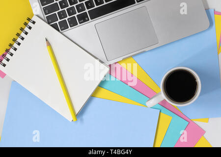 Flat lay photo of a creative workspace. Top view of a desk with multicoloured pastel paper, notepad and pencil, laptop and coffee cup with copy space. - Stock Photo