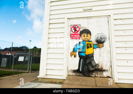 'No Boys Allowed' Graffiti by James Ame - Ame72 (The `Lego Guy)  -  on the exterior of the leisure centre in Aberystwyth, showing an unhappy boy in a GK  netball vest, in reference to the ban by the Urdd ( a welsh langiage youth organisation) on boys competing in netball competitions.  March 10 2019 - Stock Photo