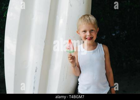 Boy eating, enjoying his watermelon ice cream in hot sunny day on summer - Stock Photo