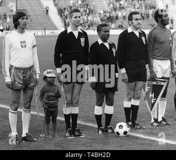 The referees and members of the Polish and Haitian national soccer teams stand in file of the national anthems before the start of the 1974 World Cup group game Poland against Haiti in Munich, Germany, 19 June 1974. From L: Polish team captain and midfielder Kazimierz Deyna, the little boy and mascot of the Haitian national team Miro, German linesman Walter Eschweiler, referee Covindasamy Suppiah from Singapore, German linesman  Ferdinand Biwersi and Haitian team captain and defender Vilner Nazaire. | usage worldwide - Stock Photo
