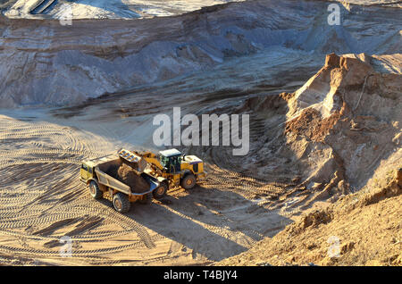 Wheel front-end loader unloading sand into heavy dump truck at the opencast mining quarry - Stock Photo