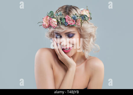 Smiling model in flowers. Beautiful young woman with short blonde curly hair and bright makeup - Stock Photo