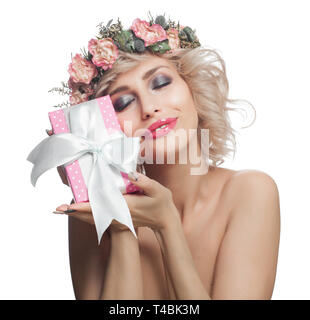 Beautiful smiling woman with pink gift. Happy cheerful woman with blonde hair, makeup and flowers isolated on white background - Stock Photo