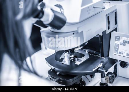 Helth care professional microscoping on hi-tec fluorescent microscope. - Stock Photo