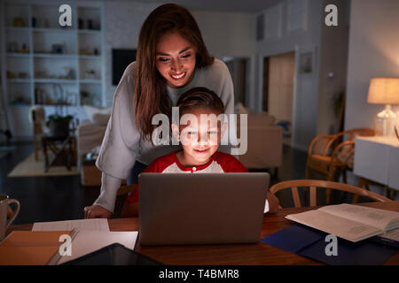 Hispanic woman looking over her son's shoulder while he does his homework using laptop computer - Stock Photo