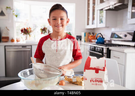 Proud pre-teen boy making cake mixture on his own in the kitchen, smiling, close up - Stock Photo