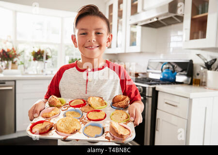 Proud pre-teen Hispanic boy standing in kitchen presenting the cakes he's made to camera, close up - Stock Photo