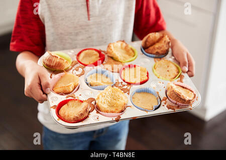 Boy holding baking tray, presenting the cakes he has baked to camera, mid section, close up - Stock Photo