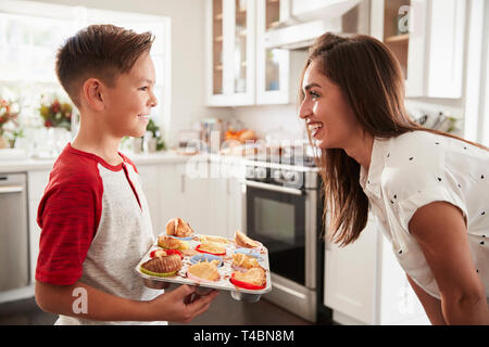 Pre-teen Hispanic boy presenting the cakes he has baked to his proud mother, close up - Stock Photo