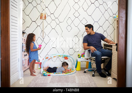 Dad working at a desk at home turns around to talk to his young kids, playing in the room behind him - Stock Photo